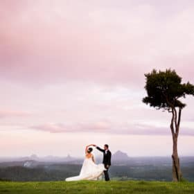 wedding couple dancing on one tree hill overlooking the sunset
